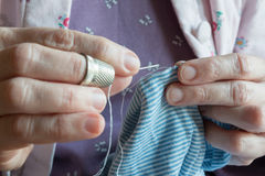 Ourlant une robe, la femme remet la couture Photographie stock