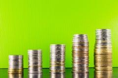 Ouro da pirâmide e moedas de prata em um desktop verde da obscuridade do fundo Imagens de Stock