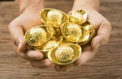Ouro do chinês da posse da mão Fotos de Stock Royalty Free