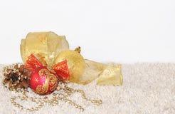 Ouro e bolas vermelhas do Natal, cone do pinho, decorações da fita em l Imagem de Stock