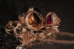 Ouro, joias em um fundo escuro Imagens de Stock
