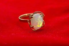 Ouro Opal Ring no veludo vermelho imagem de stock