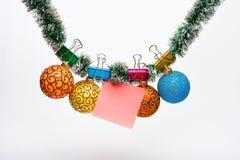 Ouropel com os ornamento do Natal e papel fixados para notas, fundo branco, espaço da cópia O Natal ornaments o conceito fotografia de stock