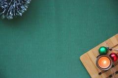 Ouropel do ` s do ano novo, bolas, uma vela ardente em um suporte de madeira em um fundo verde Lugar para a inscrição fotos de stock