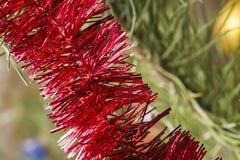 Ouropel vermelho do Natal na árvore Fotografia de Stock