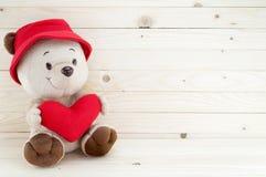 Ours au coeur rouge de prise d'amour sur le fond en bois Image stock