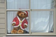 Ours d'or dans la robe de Santa Claus se tenant sur la fenêtre en bois blanche Photographie stock