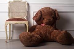 Ours de nounours énorme près d'une chaise vide Photos stock