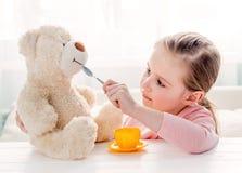 Ours de nounours de alimentation mignon de jouet de petite fille Photo stock