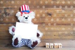 Ours de nounours américain de sourire tenant la carte blanche pour le 4ème juillet h Image stock