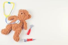 Ours de nounours avec des outils de médecine de stéthoscope de jouet et de jouet sur un fond blanc Vue supérieure Photo stock