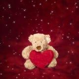 Ours de nounours avec l'oreiller en forme de coeur sur le rouge Photographie stock libre de droits