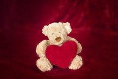 Ours de nounours avec l'oreiller en forme de coeur sur le rouge Photo libre de droits