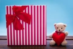 Ours de nounours avec la décoration rose de coeur sur le cadeau rose et actuel o Image stock