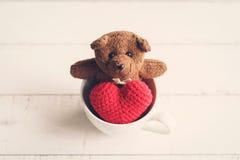 Ours de nounours avec la forme rouge de coeur dans la tasse de café Images libres de droits