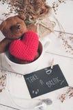 Ours de nounours avec la forme rouge de coeur dans la tasse de café Photo stock