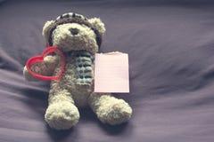 Ours de nounours avec la forme rouge de coeur et papier de note vide sur le lit Photos stock