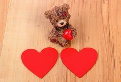 Ours de nounours avec le coeur rouge sur la surface en bois, symbole de l'amour Images stock