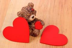 Ours de nounours avec le coeur rouge sur la surface en bois, symbole de l'amour Images libres de droits
