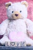 ours de nounours avec le coeur sur le fond rouge Photographie stock