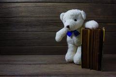 Ours de nounours avec le vieux livre sur le fond en bois, toujours la vie Images stock