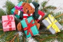 Ours de nounours avec les cadeaux colorés pour Noël et les branches impeccables Photo stock