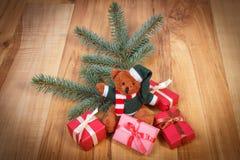 Ours de nounours avec les cadeaux colorés pour Noël et les branches impeccables Photographie stock libre de droits