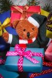 Ours de nounours avec les cadeaux colorés pour Noël et les branches impeccables Photographie stock
