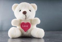 Ours de nounours blanc avec la lettre d'amour sur le fond rouge de gris de coeur Dites I vous pour le concept de jour du ` s de v Photographie stock libre de droits