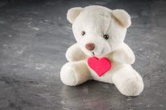 Ours de nounours blanc avec la lettre d'amour sur le fond rouge de gris de coeur Dites I vous pour le concept de jour du ` s de v Photographie stock