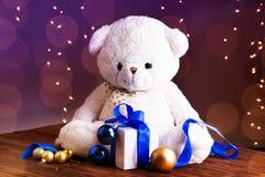 Ours de nounours blanc avec le boîte-cadeau avec le ruban bleu, l'or et le b bleu Photo stock