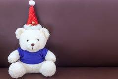Ours de nounours blanc avec le chapeau de port de Noël de chemise bleue sur le sofa Image libre de droits
