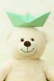 Ours de nounours blanc avec un bateau de papier sur une tête Image stock