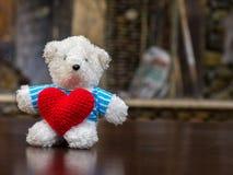 Ours de nounours blanc portant le coeur rouge de prise bleue de chemise et se reposant sur la table en bois devant l'espace de co Photographie stock libre de droits