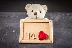 Ours de nounours blanc tenant un cadre en bois avec les numéros 14 et le coeur Fond gris Photo stock