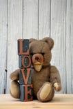 Ours de nounours brun antique se reposant avec des pierres d'amour Photographie stock