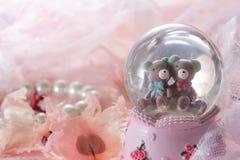 Ours de nounours dans la décoration de globe de neige sur le fond rose de tissu Image libre de droits