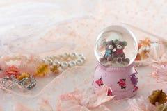 Ours de nounours dans la décoration de globe de neige sur le fond rose de tissu Image stock
