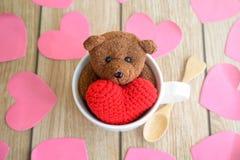 Ours de nounours dans la tasse de café avec la forme rouge de coeur sur la table en bois Photographie stock libre de droits