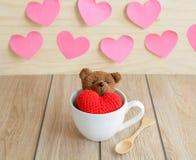 Ours de nounours dans la tasse de café avec la forme rouge de coeur sur la table en bois Images stock
