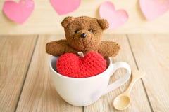 Ours de nounours dans la tasse de café avec la forme rouge de coeur sur la table en bois Photos stock