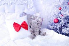 Ours de nounours dans le lit près de l'arbre de Noël photos stock