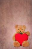 Ours de nounours de Brown avec le coeur mou sur le fond texturisé Photo libre de droits