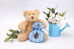 Ours de nounours de composition le 8 mars - avec des fleurs Images stock