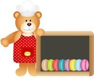 Ours de nounours de cuisinier avec le panneau d'ardoise de macarons Images stock