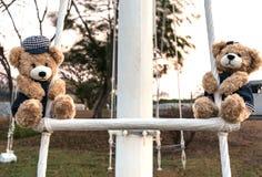 Ours de nounours de garçon et de fille accrochant dans le terrain de jeu Image stock