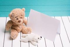 Ours de nounours deux se reposant sur le plancher en bois blanc à l'arrière-plan bleu-vert avec la note vide Photographie stock