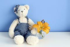 Ours de nounours doux avec une fleur dans un verre à un arrière-plan bleu Photographie stock