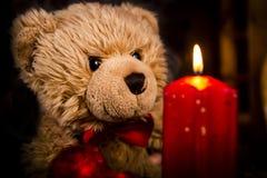 Ours de nounours et une bougie brûlante rouge photo stock