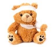 ours de nounours de jouet avec le bandage d'isolement sur le fond blanc image libre de droits